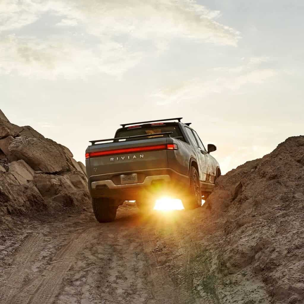 Rivian R1T truck driving up a mountain road during a sunset.