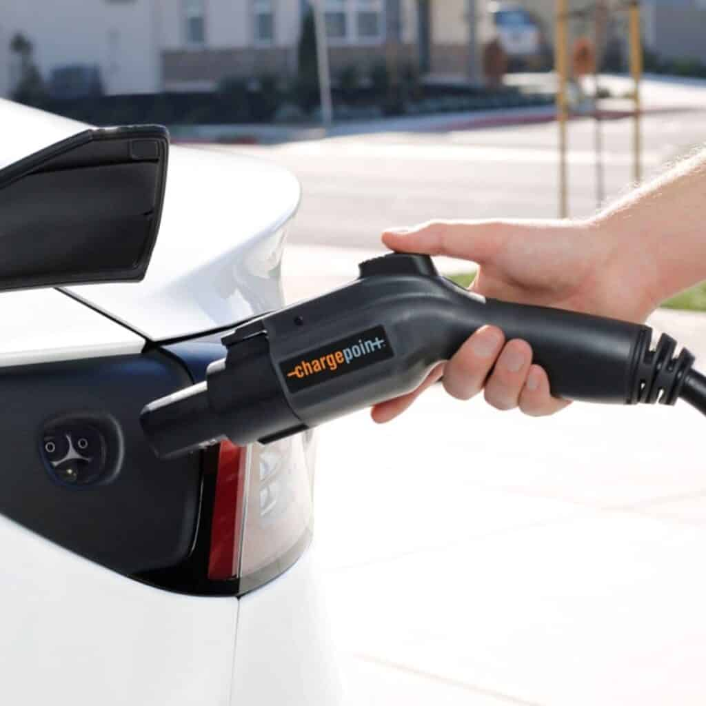Close-up of a person using a ChargePoint electric vehicle charger.