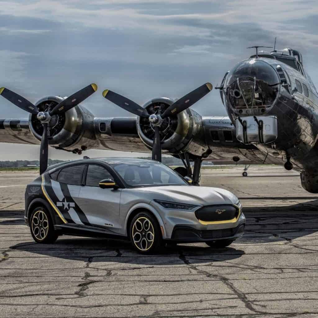 Custom Ford Mustang Mach-E in front of an airplane.