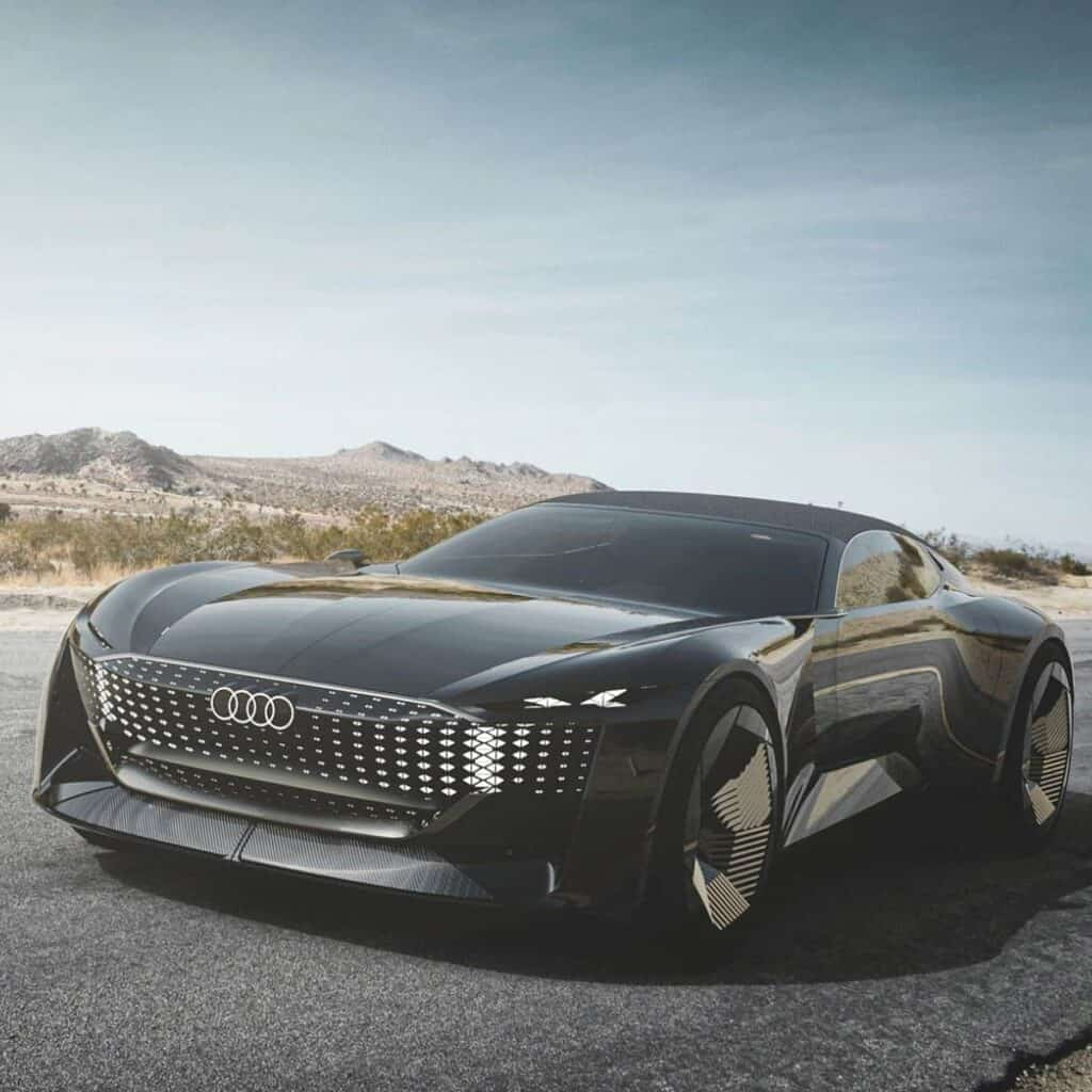 Front and side view of an Audi Skysphere parked on a mountain road.