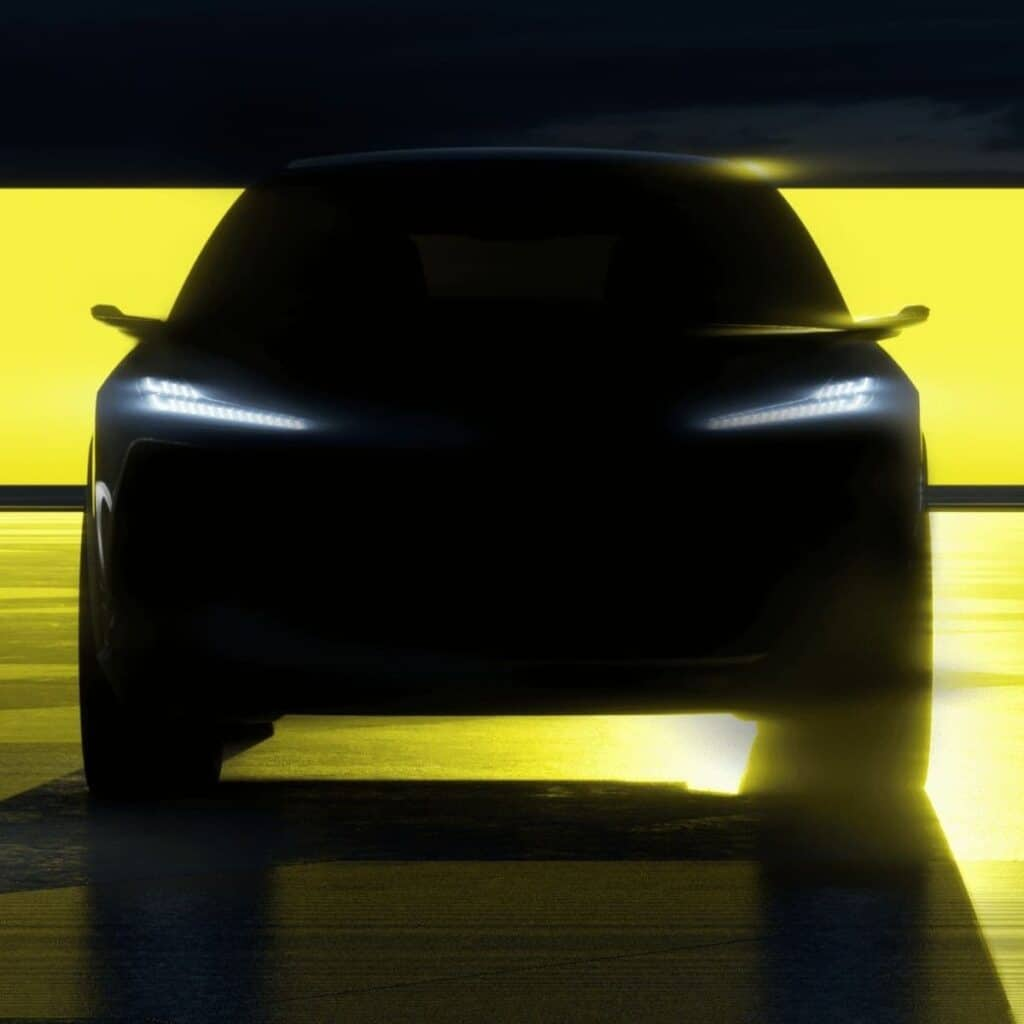SIlhouette of an SUV with its headlights on.